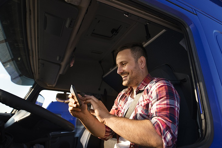 Truck driver using tablet for GPS navigation to the destination.